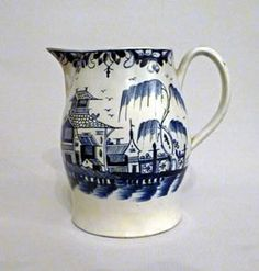 pearlware jug probably made in Liverpool. The jug is painted in underglaze blue with a group of oriental buildings to one side. There is an intricate leaf border & scrolling to the handle.    This piece is illustrated by Lois Roberts in Painted in Blue Figure 129.