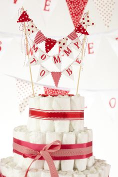 Love-Themed Diaper Cake. A diaper cake and heart line banner are the perfect backdrop to a baby shower with friends and family. Made with 100 HUGGIES® Little Snugglers Diapers.