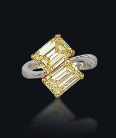 A TWIN-STONE COLOURED DIAMOND RING, BY GRAFF   Set with two fancy intense yellow rectangular-cut diamonds, each weighing approximately 2.04 carats, to the gold hoop, ring size 5¼, in black leather Graff case  Signed Graff, no. 9545 by shawna