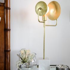 A tall, sculptural brass and marble lamp for bedside lighting