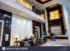 Download this stock image: Chicago Illinois Downtown Magnificent Mile Trump International Hotel & Tower hotel luxury five-star rating condo-hotel lobby man woman guest bellhop c - ENCG0N from Alamy's library of millions of high resolution stock photos, illustrations and vectors.