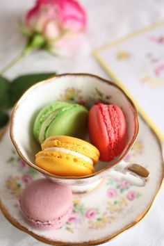 An assortment of lovely macarons handing out in a beautiful teacup.