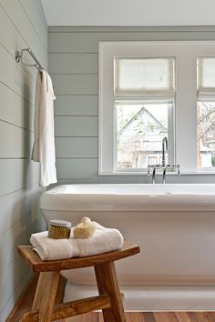 Restful bathroom with shiplap clad walls painted gray green, Benjamin Moore Tranquility, accented with a chrome towel rail over the foot of the pedestal tub with floor mount tub filler flanked by a rustic zen style stool adorned with a fresh white towel and bath scrubs.