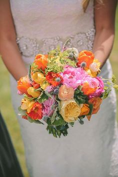 A colorful bouquet that included peonies, ranunculus, and thistle | Brides.com