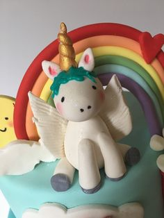 Fondant unicorn cake topper sits in front of a colorful fondant rainbow.