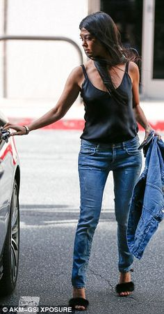 Windy weather: The Calabasas socialite paired her fuzzy feet with a sultry black silk camisole tucked into ripped blue jeans