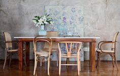 O cimento queimado das paredes ganha o aconchego da madeira presente nas cadeiras desparceiradas. Projeto da arquiteta Fernanda Neiva
