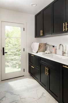 Black shaker laundry room cabinets accented with brushed gold pulls are mounted over a sink with a satin nickel faucet mounted to a white quartz countertop over black shaker lower cabinets.Black shaker laundry room cabinets accented with brushed gold Laundry Room Remodel, Laundry Room Cabinets, Laundry Room Organization, Laundry Room Design, Kitchen Remodel, Black Cabinets Bathroom, Home Decor Kitchen, Kitchen Interior, White Laundry Rooms