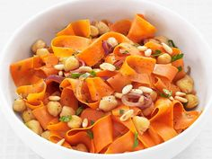 To make this recipe for Carrots with Chickpeas and Pine Nuts, use a peeler to shave carrots into thin ribbons, and top with chopped parsley and pine nuts to make a fresh, colorful side dish.