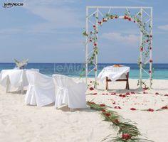 http://www.lemienozze.it/gallerie/foto-fiori-e-allestimenti-matrimonio/img31128.html La spiaggia come location per celebrare le nozze. Ecco un allestimento con arco di rose rosse.