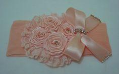 Faixa em meia de seda salmon com flores e laço em fita com detalhes dourados para deixar sua princesa encantada.