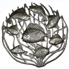 Hand cut and embossed by Haitian artisans, this 24-inch wall art features a school of fish in coral. The natural patina makes this piece perfect for hanging indoors or out.
