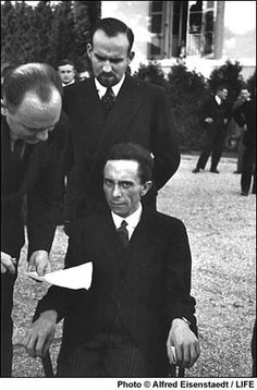 """At a League of Nations conference in 1933, Nazi Propaganda Minister Joseph Goebbels remains seated while speaking to his interpreter.  German-born photographer Alfred Eisenstaedt, later one of the founder of LIFE, recalled that Goebbels smiled at him until he learned that Eisenstaedt was Jewish--a moment Eisenstaedt captured in this photo.  Suddenly, """"he looked at me with hateful eyes and waited for me to wither.  But I didn't wither."""""""