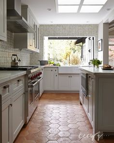 Rustic cottage kitchen features four skylights situated over an island topped with white marble lined atop a terracotta hex tile floor.