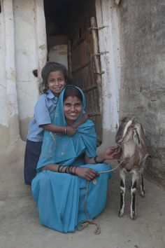 Heifer project members, Sumitra Devi andfive-year-old daughter Anita happily pose for a photo with their family's goat.
