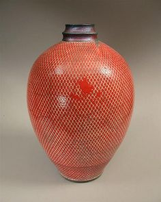 Vermillion by Paul Schneider. This piece was *wheel thrown* using balcones white clay from South Texas. The vermillion is stenciled in order to achieve the unique pattern. The glaze firing utilized the *raku* method, which sees the kiln temperature rise to 1840 degrees Fahrenheit in less than an hour. Due to the quick and low temperature firing the piece retains some porosity. This vase is not suitable to contain liquids.