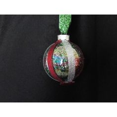 Handcrafted glass ornament is glitter lined with silver and red ribbons wrapped around the outside with a red star gemstone attached to the bottom. Glitter Ribbon, Green Glitter, Fabric Ornaments, Ball Ornaments, Ribbon Wrap, Red Ribbon, Handcrafted Christmas Ornaments, Glass Ball, Christmas Bulbs