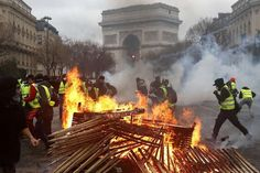 Demonstrators run by a burning fire near the Arc de Triomphe during a fresh protest which has seen Yellow Vest supporters clash with riot police and more than 100 people arrested so far on Saturday Transformers, Riot Police, French President, Triomphe, A Level Art, Paris Street, Africa Travel, Photos, Socialism