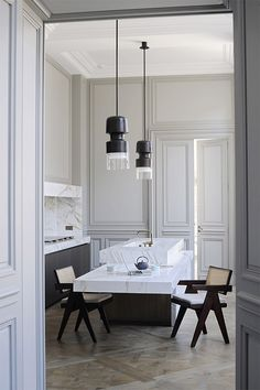 Joseph Dirand Paris luxe minimal kitchen white marble gray molding Pierre Jeanneret chairs bronze pendants http://amzn.to/2keVOw4