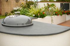 A kettle style bbq that is sunk into a custom cut slate work surface in a semi circle with smoothed edges so that you can enjoy eating outside with minimal fuss all year round.