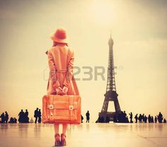 vintage: Redhead girl with suitcase on Eiffel tower background