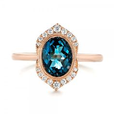 #103173 This stunning women's fashion ring features an oval London blue topaz bezel set in the center, surrounded by a double ring of milgrain beading and a modified halo of...