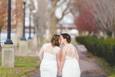 Two brides outdoor wedding day photo - photo from behind of two brides sharing a kiss while holding hands outside {Jay Zhang Photography}