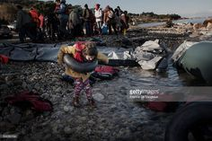 A young girl plays with a tire air chamber amid dinghy debris after she landed on Lesbos near Mytilene airport as other refugees from Afghanistan and Syria wait to be shuttled to a registration camp by bus, Greece on 08 January, 2016. Lesbos, the Greek vacation island in the Aegean Sea between Turkey and Greece, faces massive refugee flows from the Middle East countries.