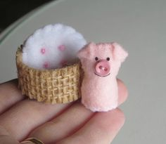 My sweet little pig measures just 1 1/4 tall. Its carefully stitched from felt and stuffed with polyester fiberfill. Theres detailing with threads, a cute little curly embroidery floss tail, and a tiny button nose.  The cozy little basket (which is stiffened to be more durable) is felt covered with burlap. The pillow is also made from felt.    wishwithme creations are carefully put together with attention to quality, detail and like all items in my shop, are designed and created by me alone…