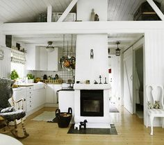 Small Scandinavian Cottage. White planked walls & valted, beamed ceilings really open-up this small space. The central fireplace is the center of attention without having to arrange furniture around it. 3of4