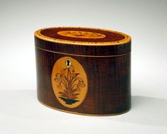 A fine mahogany tea caddy with floralmarquetry inlay.    Height: 4 1/2 inches  Width: 6 1/2 inches  Depth: 3 3/4 inches