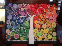 Auction project for elementary school. Students studied rotational symmetry. Pastel on colored paper for leaves. Large (4'x5') pre-stretched, pre-gessoed canvas I painted all black with acrylic. Tree and branches painted with white acrylic. Filled in empty spaces with small circles of pastel on colored paper.  - Sarah Smith