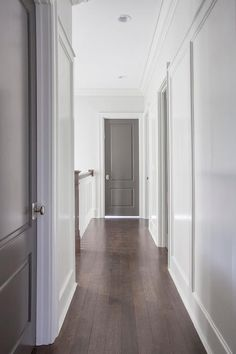 Chic hallway features white walls fitted with gray paneled doors adorned with polished nickel door knobs.