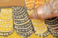 Intercale as tintas metálicas ouro e cobre nas penas da parte inferior da tela e faça traços e bolinhas para formar as listras nas penas.