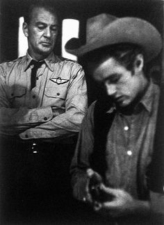 GIANT (1956) - James Dean examines a six shooter during a visit to the 'Giant' set by Gary Cooper who was shooting 'The Court Martial of Billy Mitchell' on the Warner Bros. lot - Publicity Still.