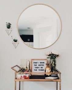 Round gold mirror with hanging plants and gold bar cart