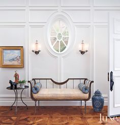 In the entry, white paneled walls begin with the top-floor crown molding and drop down to the wine cellar.