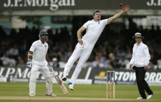England's James Anderson, center, reaches out to collect the ball on the third day of the first test cricket match between England and Sri Lanka, at Lord's cricket ground in London, Saturday, June, 14, 2014.