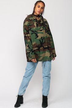 """Vintage army jacket in a camo print with a hood. Pullover style with a drawstring waist. Works for men or women.  Every item we sell is authentic vintage and one-of-a-kind! You will receive the EXACT item shown in the photos. For reference, model is 5'8"""" and measures 32-23-34. DETAILS  Best fits: marked medium, fits large (Note: We only have ONE in stock. If more than one size is listed it is because this item will work on a range of sizes. Check measurements for exact fit.) Condition: very…"""