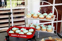 Backyard Barbecue First Birthday Party: vanilla cupcakes with light blue frosting and blue and red flags, served in a mini radio flyer wagon