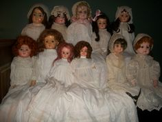 This group of dolls are all wearing antique christening gowns