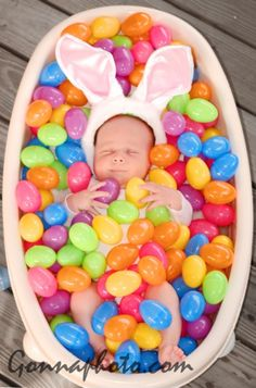 I don't know about the ears, but I like the idea of the baby being surrounded by plastic eggs! Cute Easter Picture!