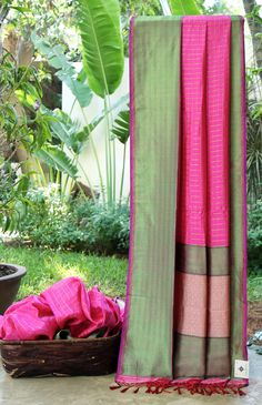 This Benares silk is in hot pink that is chequered with gold zari. The border and pallu are in green, gold zari and hot pink balancing the bright base and making this a much sought after piece.