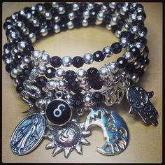 Stack of sterling silver ball and faceted onyx bracelets with charms www.jacyandjools.co.uk