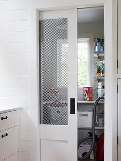 this closet features a white chicken wire pocket door which opens up to a utility closet
