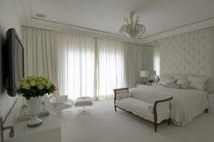 Quarto todo branco + cabeceira de tecido com capitonê + espelho do piso ao teto. Projeto Roberto Migotto.