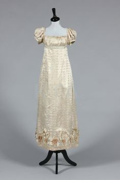 An ivory figured silk gown circa 1815-20, signed to the inner waistband 'Peyron', empire line with puff sleeves, the hem with elaborate embossed silk petals, silk rose centres. (Up for auction October 14, 2013 at Kerry Taylor auctions!