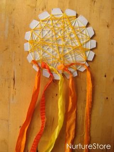 Wrap / weave thread onto a circle with notches cut out then tie ribbons on it