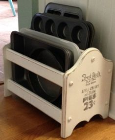 Repurposed magazine stand to hold muffin tins --- I have one of these.... it was my grandmothers.... of course.... is 'brown'..... ooooo I think I just might!