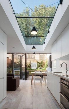 The rear extension to this lower-ground floor flat offers a vista of trees and sky through a long rooflight as well as an adjacent oval version, while full width bi-fold doors create a seamless connection t the beautifully landscaped courtyard garden Modern Kitchen Design, Interior Design Kitchen, Kitchen Designs, Kitchen Contemporary, Interior Garden, Coastal Interior, Minimal Kitchen, Bohemian Interior, Modern Interior Design